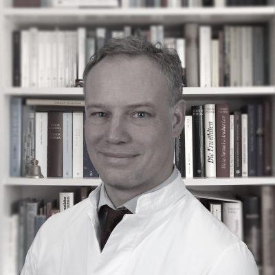 Dr.Dissmann vor Bücherregal klein